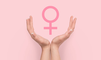 Woman hands holding female gender sign on pink background.