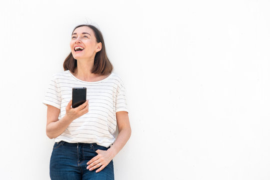 happy middle aged woman holding cellphone by white background