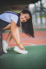 asian teenager wearing sneaker shoe in indoor sport club