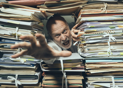 Panicked businessman overloaded with paperwork