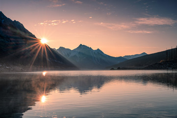 Zelfklevend Fotobehang Ochtendgloren Sunrise on mountain with foggy in Medicine lake at Jasper