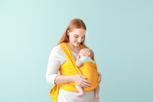 Mother with cute baby on color background