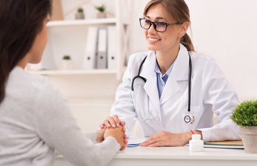 Positive Doctor Woman Comforting Patient During Appointment In Office