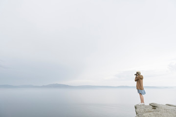Woman with camera standing on rock, taking pictures of the sea, rear view