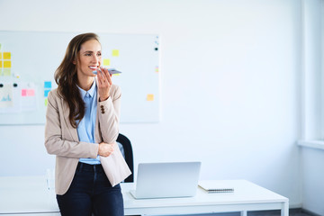 Young woman leaning on desk in office during phone call
