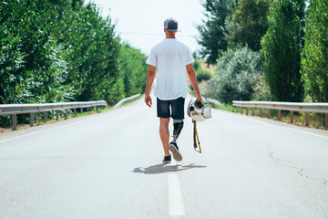 Young man with leg prosthesis walking along the road with a helmet