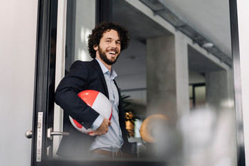 Happy businessman holding beach ball in office