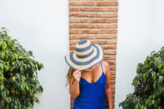 Woman wearing blue dress and straw hat standing in front of wall, Nerja, Spain