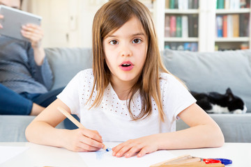 Portrait of girl drawing with coloured pencil at home