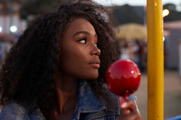Portrait of young woman candied apple at fair in the evening