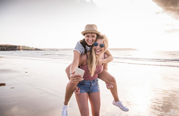 Two girlfriends having fun on the beach, carrying each other piggyback, taking smartphone selfies Papier Peint