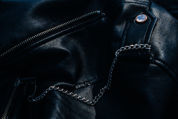 Silver chain pinned to black leather jacket