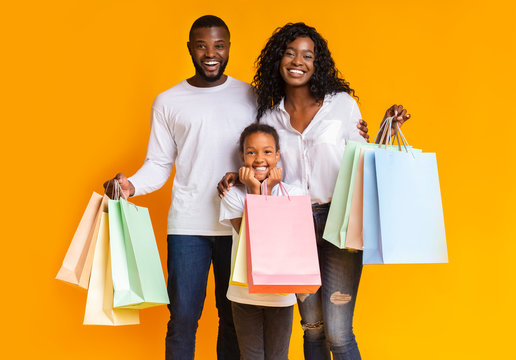 Portrait of happy african american family holding shopping bags