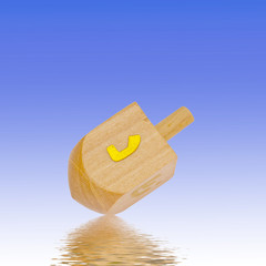 Dreidel on bright background, blue, reflection. Judaism, religious equipment, item.