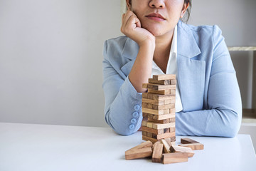 Alternative Risk and Strategy in Business, Image of Stressed, worry, Business woman gambling placing making wooden block hierarchy on the tower to planning and development to successful