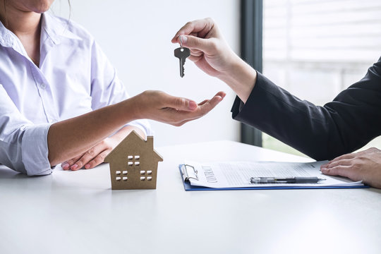 Estate agent giving house keys to client after signing agreement contract