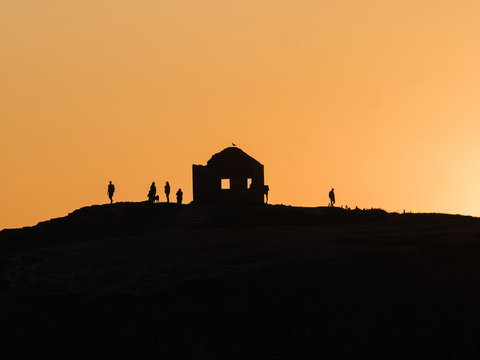 Silhouettes of people on top of hill