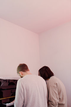 Rear view of man and woman playing piano together