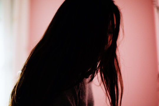Side view of woman covering face with her hair