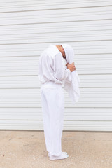 Man in white standing with towel on head