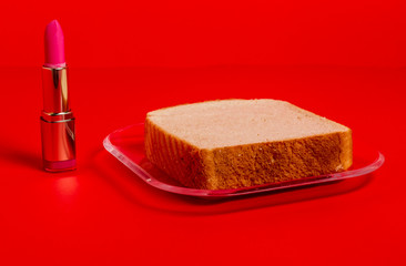 Slice of bread and pink lipstick on red surface