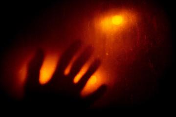 Hand on glass in dark room