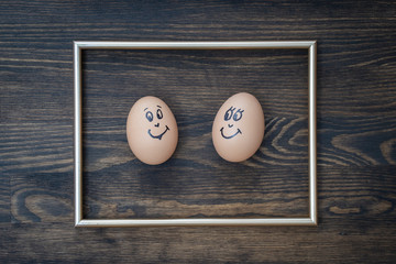 Picture golden frame and two funny eggs smiling on dark wooden wall background. Eggs family emotion face portrait. Couple eggs with happy face for love concept