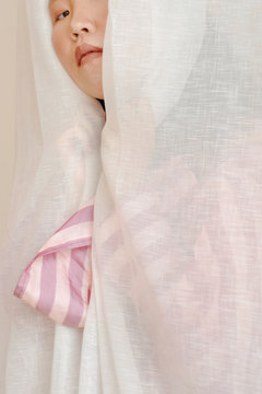Portrait of woman in pink shirt hiding behind white curtain