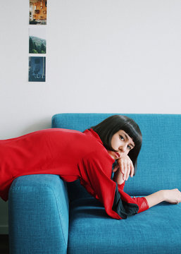 Portrait of stylish woman in red dress leaning on blue sofa