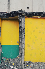 Demolished building with hand prints on yellow wall