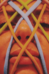 Close up of face crossed with colorful shoe laces