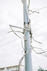 Low angle view of utility pole covered in extension cords