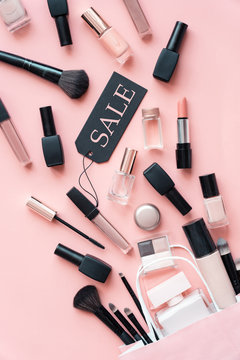 Makeup cosmetic perfume women products accessory pouring from shopping bag on pink flat lay background, beauty products cheap discount retail offer online purchase, top view above vertical photo
