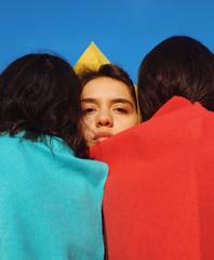 Woman looking over shoulders of friends