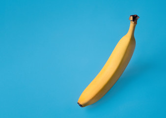 Banana and its shadow on blue surface