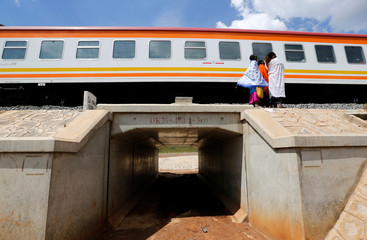 Women stand next to a train on the Standard Gauge Railway line in Kimuka
