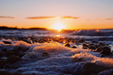 Close up of sea foam on beach at sunset