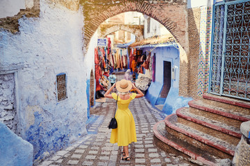 Colorful traveling by Morocco. Young woman in yellow dress walking in medina of blue city Chefchaouen.