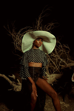 Woman in large patterned straw hat sitting on branch at night