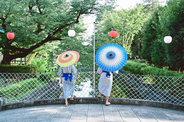 Rear view of siblings with parasols standing near chainlink fence