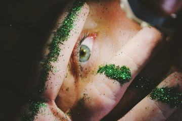 Close up view of human eye seen between fingers sprinkled with  glitter