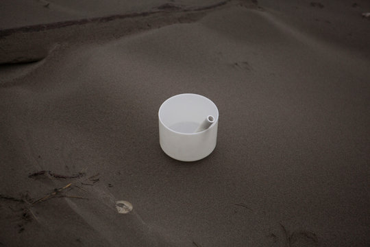 Composition of white vessel with pipe on black sand