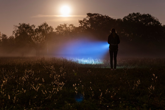 A person with a flashlight on a foggy meadow, with a flashlight in the fog, foggy meadow with moonlight
