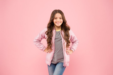 Cute and stylish. Happy baby girl smile on pink background. Brunette girl with long wavy hair in casual autumn style. Cute little girl of fashion. Small girl with beauty look
