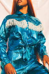 Midsection of model wearing metallic blue outfit with fringe