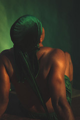 Rear view of shirtless man in dorag sitting in green light