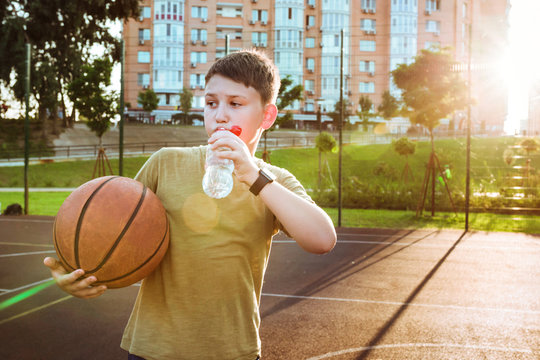 Teenage boy on a playground with a basketball and a bottle of water, on a sunny day. Healthy lifestyle and sport concepts.