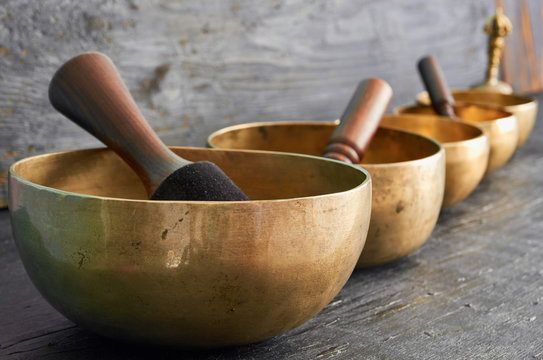 Tibetan singing bowls with sticks on the dark background - music instruments for meditation, relaxation after yoga practice and healing massage