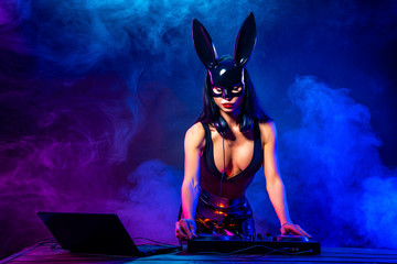Young sexy woman dj playing music in mask. Headphones and dj mixer on table. Smoke on background