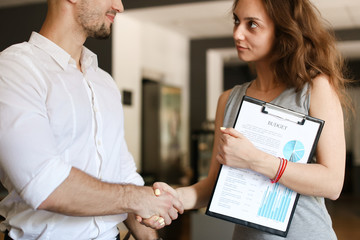 Young businessman shaking hands with female manager.
